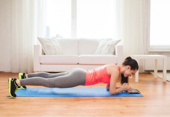 Woman doing plank pose in her living room.