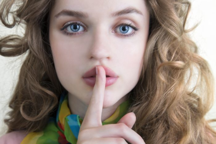 Teenage Girl Gesturing For Silence With Her Finger In Front Of Her Mouth