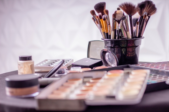 A collection of beauty tools and makeup sits on a table.
