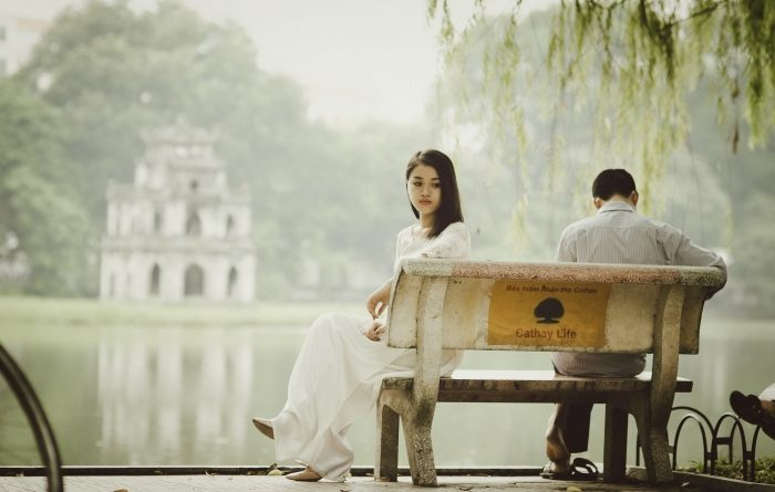 A man and woman sit on a bench after a breakup.